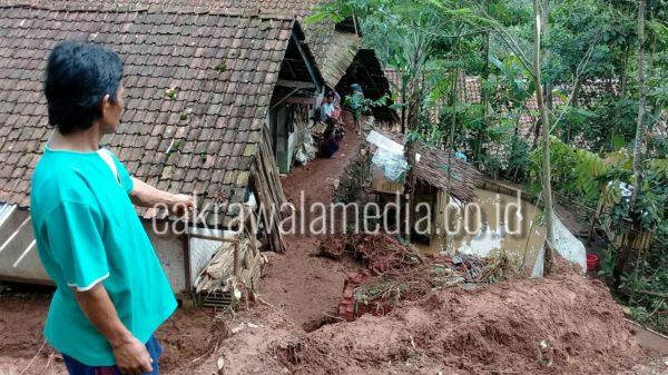 Salah seorang warga menunjukan longsoran tanah yang mengancam sedikitnya 10 rumah dibawahnya . ( foto dezaf )